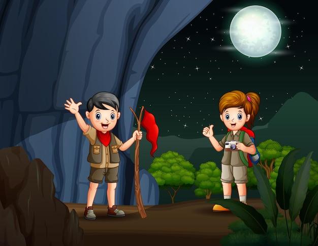 スカウトの男の子と女の子が洞窟でハイキング