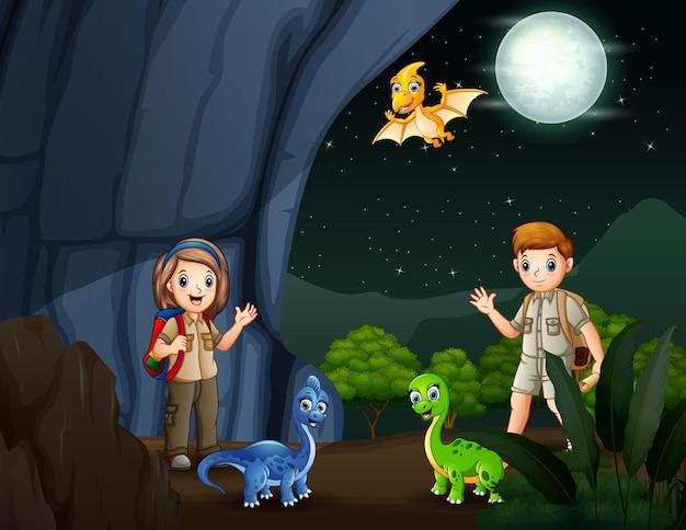 夜の洞窟にいるスカウトと多くの恐竜
