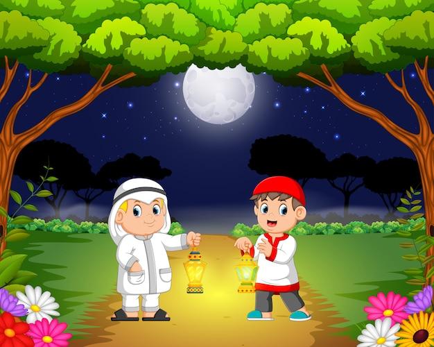 두 아이들이 정원에서 만나서 라마단 랜턴을 들고 있습니다