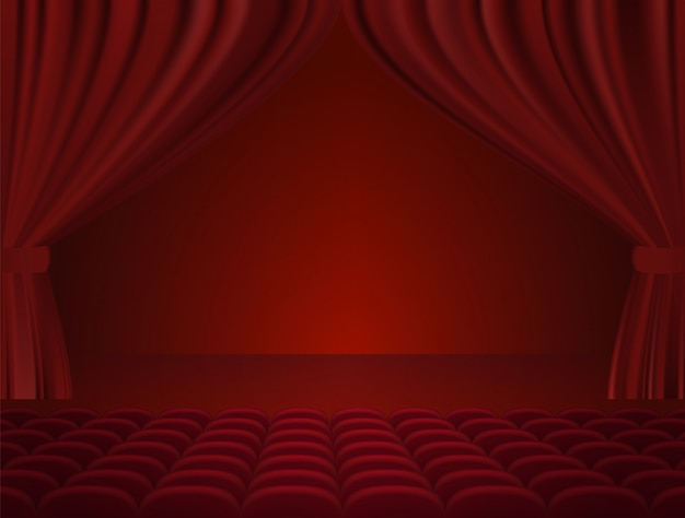 Theater interior with red curtains and seats.