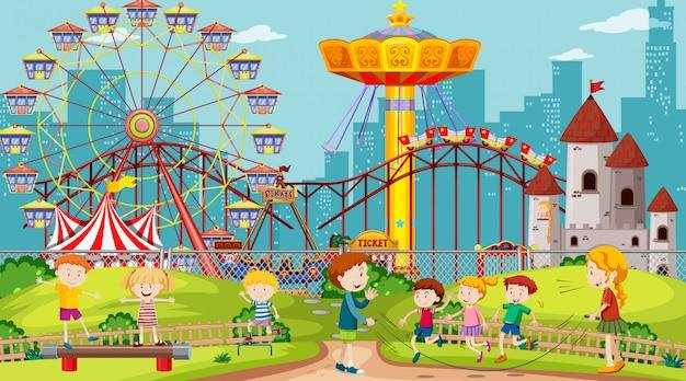 놀이기구와 행복한 아이들이 많은 테마파크 장면