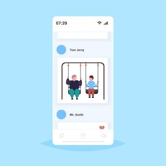 Толстые и толстые мужчины пара качается вместе ожирение концепция избыточный вес мужчина с другом, сидя на качелях, с удовольствием экран смартфона онлайн мобильное приложение полной длины