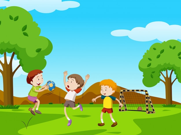 Три мальчика играют в мяч в парке