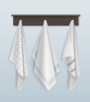 Three clean cotton or linen white and polka dots towels hanging on brown wooden hook on blue wall