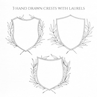 Three hand drawn crests with laurels for a wedding design