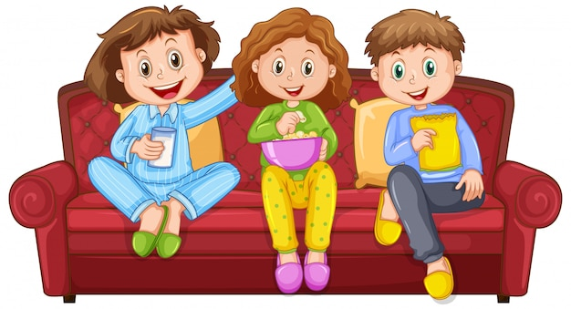 Three happy kids eating snacks on the sofa
