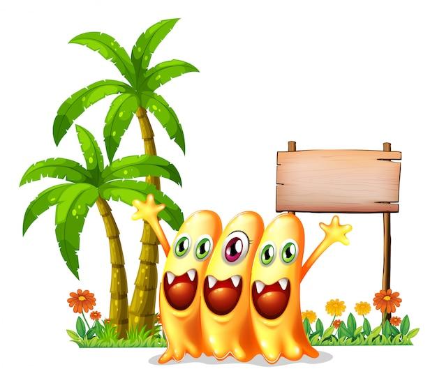 空の木製看板の前に3つの幸せなオレンジモンスター