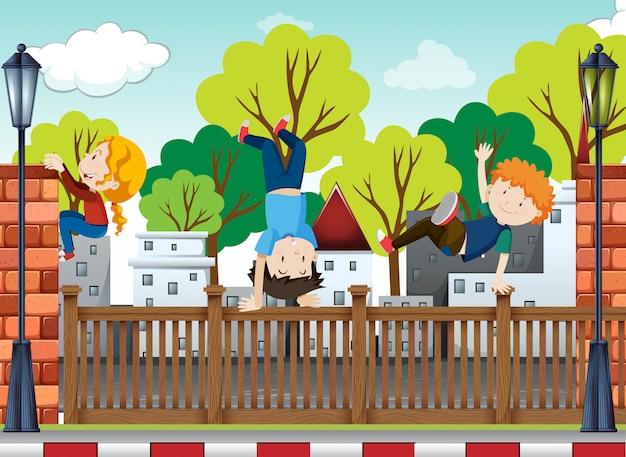 3人の子供たちが踊り、舗装の上にひっくり返る