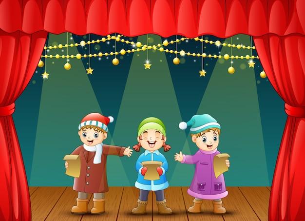 Three kids singing christmas carols on stage