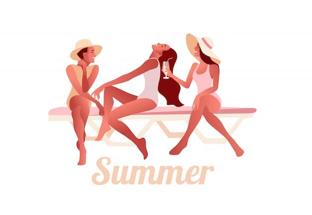 Три сексуальные молодые девушки в летних шляпках беседуют на пляже и пьют коктейли