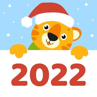 Тигр в шапке санта-клауса с новым годом животное держит белый пустой плакат