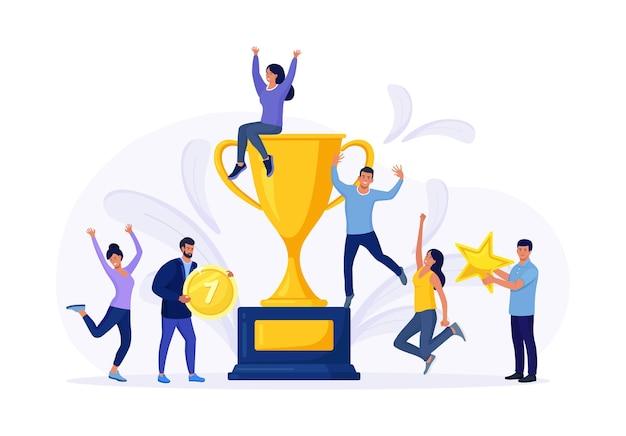 小さなビジネスマンは、大きな黄金のトロフィーの周りの勝利を祝います。チャンピオンカップを獲得した人々のグループ。目標達成、成功したチームワークのお祝い。史上最高のチーム
