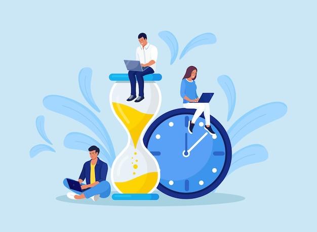 작은 사람들과 거대한 모래 시계, 알람 시계. 노트북과 함께 작업하는 팀. 시간 관리 및 사업 계획. 시간은 돈이다. 마감 시간. 젊은 직원들은 큰 시계의 다이얼 근처에서 일합니다.