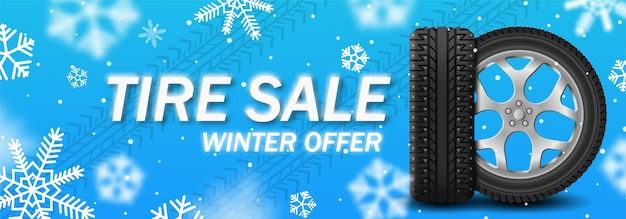 Tire sale winter banner with car wheel with spikes on winter blue background with snowflakes