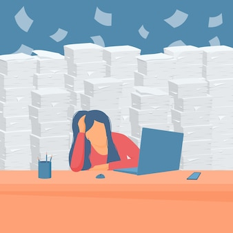 Tired girl worker bowed her head at the office table against the backdrop of piles of paper