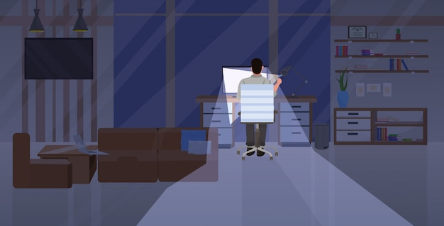 Tired man sitting at workplace rear view businessman working on computer at night deadline overwork concept modern office interior flat horizontal