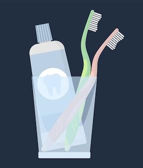 Зубные щетки с зубной пастой, стоящие в прозрачном стакане