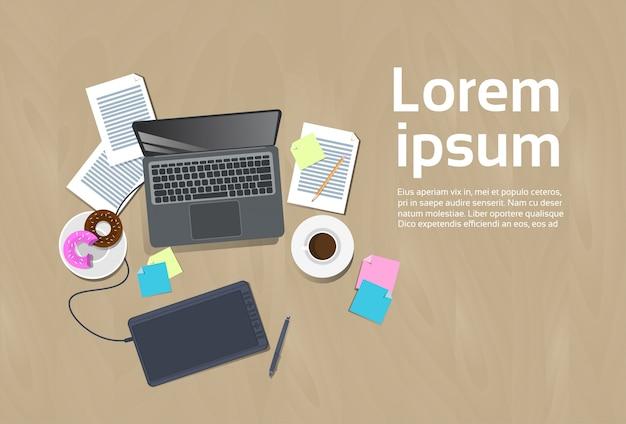 デジタルタブレットとスタイラスペン、テンプレートワークスペースの背景概念とデザイナー職場ラップトップのトップアングル