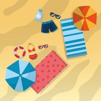 Вид сверху на пляж с купальниками, зонтик, солнцезащитные очки, полотенца и бутылка солнцезащитного крема.