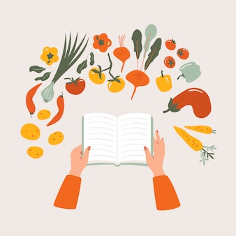 Top view of cartoon cookbook in hand on the table surrounded by various vegetables.