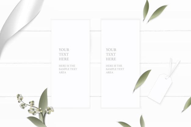 Top view elegant white composition paper flower leaf tag and silver ribbon on wooden background.