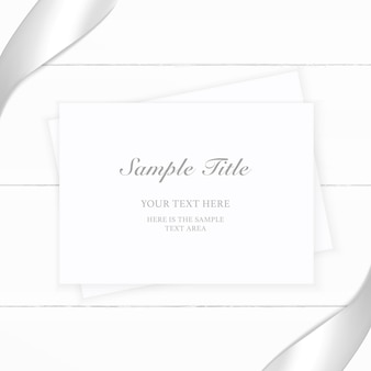 Top view elegant white composition paper silver ribbon on wooden background.