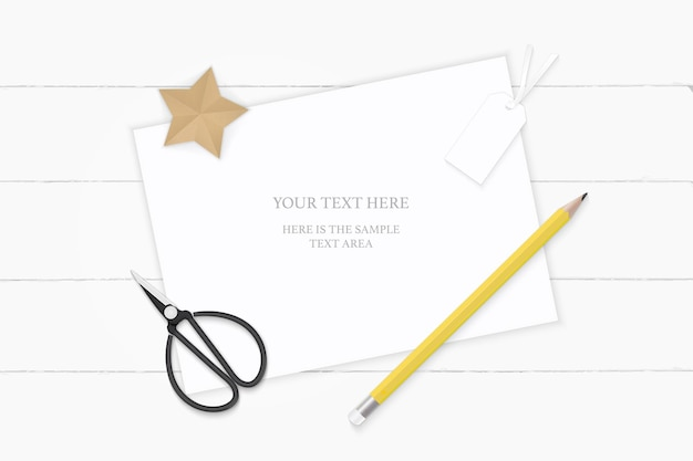 Top view elegant white composition paper tag yellow pencil star craft and vintage metal scissors on wooden background.