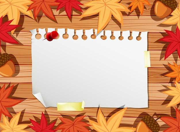 Вид сверху чистого листа бумаги на столе с элементами осенних листьев