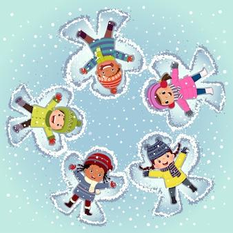 Вид сверху на детей, лежащих и лепящих снежного ангела на снегу в зимний день
