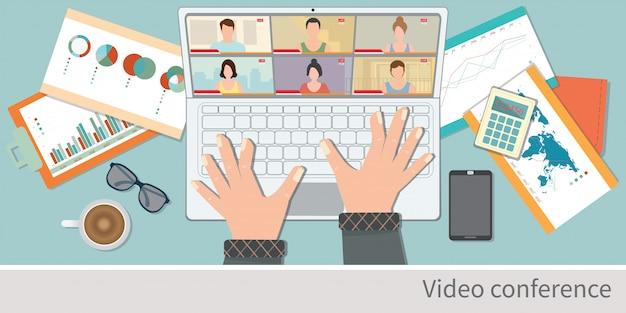 自宅でビデオ会議用のラップトップを使用している人間の手の平面図。