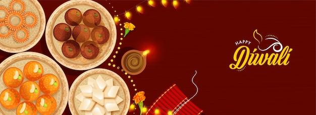 幸せなディワリ祭のお祝いのために、点灯したオイルランプ(diya)、爆竹の縞模様、赤い背景にガーランドを照らしてインドのお菓子を提示する上面図。