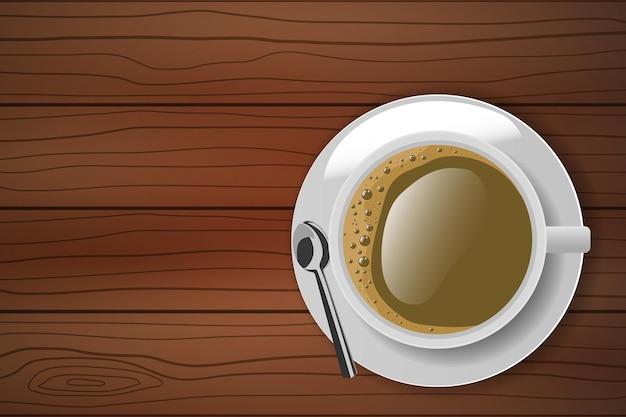 木製のテーブルの上のプレートとスプーンと白いコーヒーカップの上面図