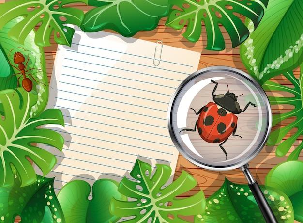 Вид сверху деревянного стола с чистым листом бумаги и элементом насекомых и листьев