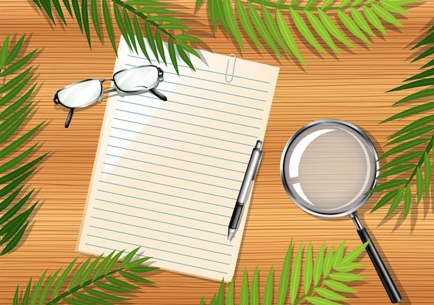 白紙とオフィスオブジェクトと葉の要素と木製のテーブルの上面図