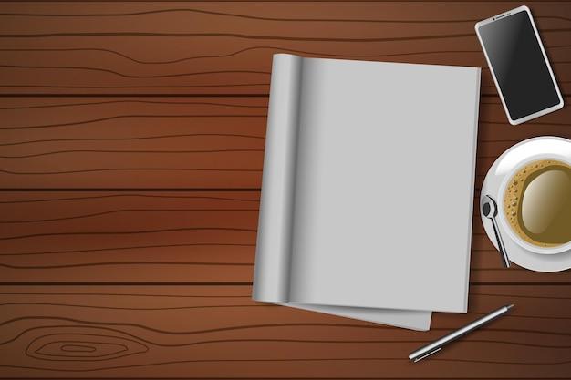 開いた空白のノートブック、ペン、コーヒーカップ、スマートフォンと木製のテーブルの上面図。