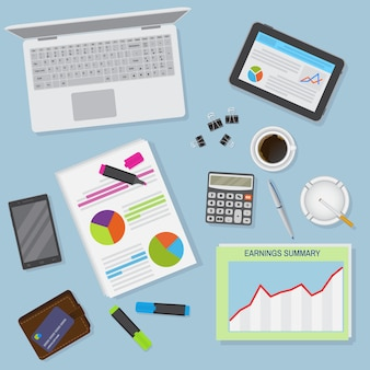 Top view of office desk background including laptop, digital devices, financial and business objects.