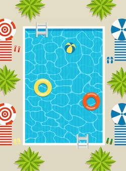 Top view of pool with sun loungers and umbrellas, palm trees and inflatable circles in the water.
