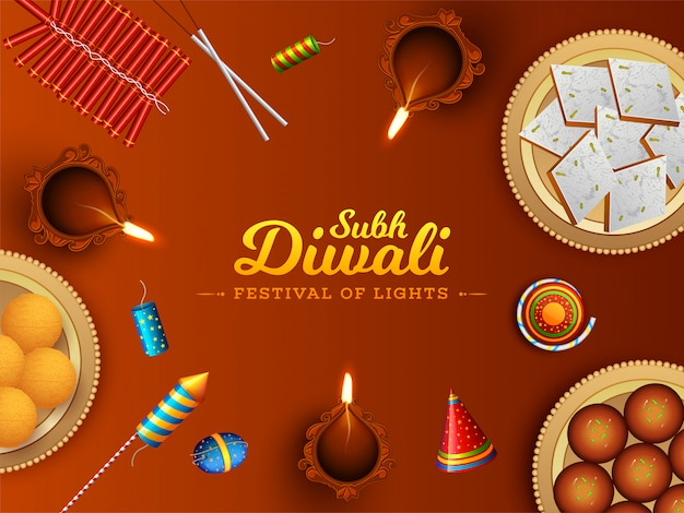 Top view of sweets with firecrackers and illuminated oil lamp (diya) for festival of lights, subh diwali celebration concept.