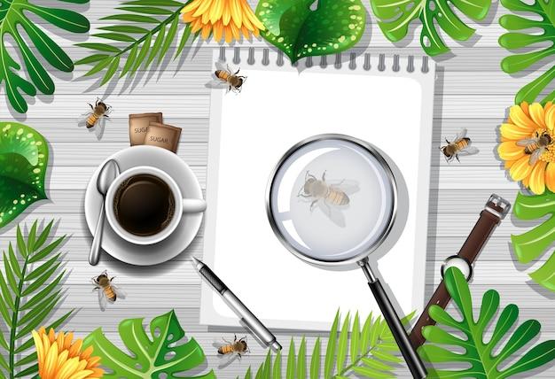 Vista dall'alto del tavolo in legno con elementi per ufficio e foglie e insetti