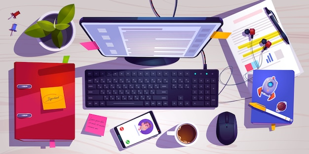 Top view of workspace with computer, stationery, coffee cup and plant on wooden table.