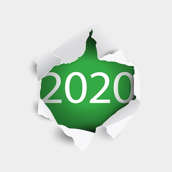 Torn white paper hole with new year inscription 2020 on green