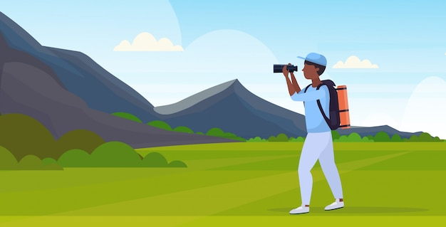 Tourist hiker with backpack looking through binoculars hiking concept african american traveler on hike beautiful mountains nature landscape background full length flat horizontal
