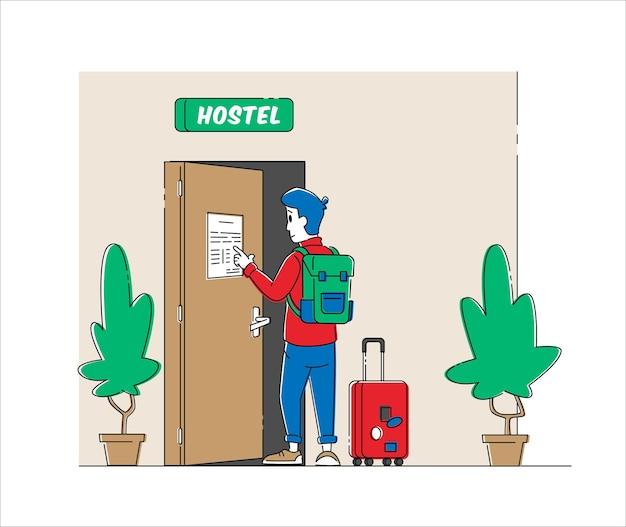 Турист с багажом читает заметки или правила в холле хостела