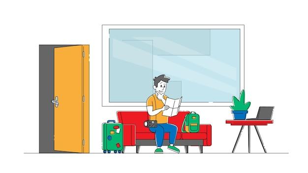 Турист с багажом, сидя на диване в лобби хостела, обучающая карта