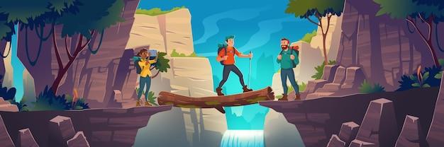 Туристы пересекают бревенчатый мост между горами над скалой в пейзаже скальных вершин с водопадом и деревьями. девушка сделать картину красивого пейзажа с видом на природу.