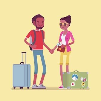 荷物とスーツケースを持って旅行する衣装の観光客