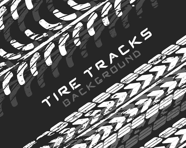 Следы автомобильных шин и треков на черном фоне. реалистичная композиция следов. мотокросс, велосипедная дорожка, автомобильная трасса или автогонки. автосервис смена шин. значок транспортного средства - минимальный символ.