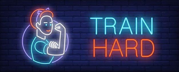 Train hard neon sign. strong woman touching her biceps on dark brick wall.
