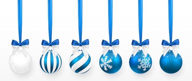 雪の効果と青い弓がセットされた透明で青いクリスマスボール。白い背景の上のクリスマスのガラス玉。休日の装飾テンプレート。