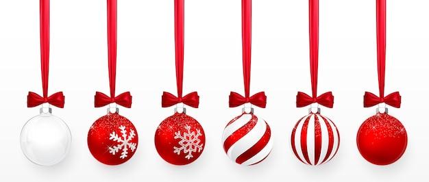 雪の効果と赤い弓がセットされた透明で赤いクリスマスボール。白い背景の上のクリスマスのガラス玉。休日の装飾テンプレート。